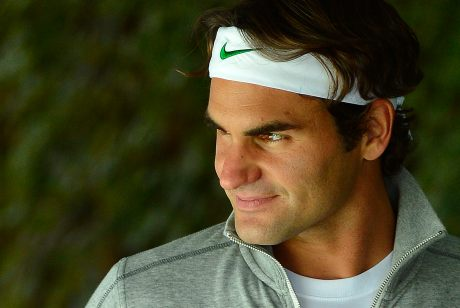 Roger Federer of Switzerland looks out across practice courts at Wimbledon in London